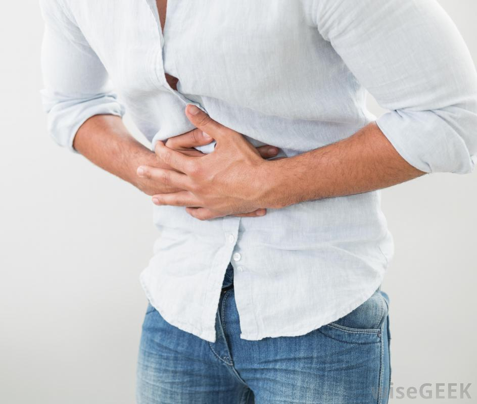 person-in-white-shirt-and-jeans-with-stomach-pain-against-white